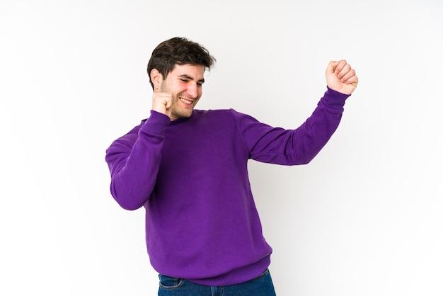 Junger mann isoliert auf weißer wand tanzen und spaß haben.