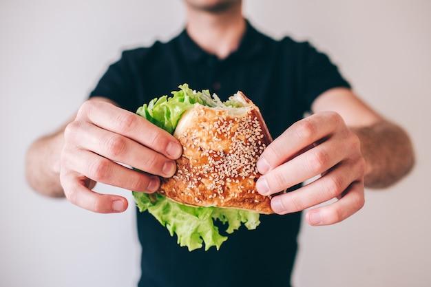 Junger mann isoliert. schnittansicht des kerls, der brötchen mit grünem salat hält. leckeres leckeres sandwich.