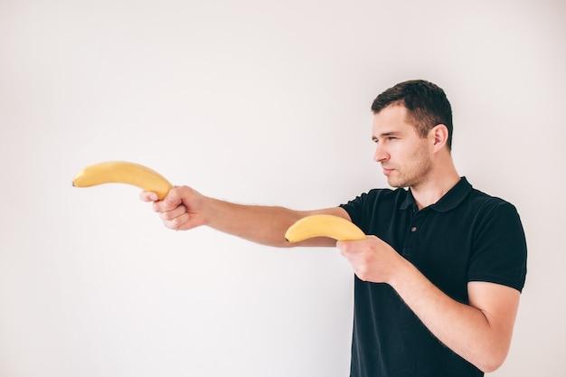 Junger mann isoliert über weiß. seitenansicht des kerls, der zwei gelbe reife bananen hat und sie als waffe hält. ernst konzentrierter mann.