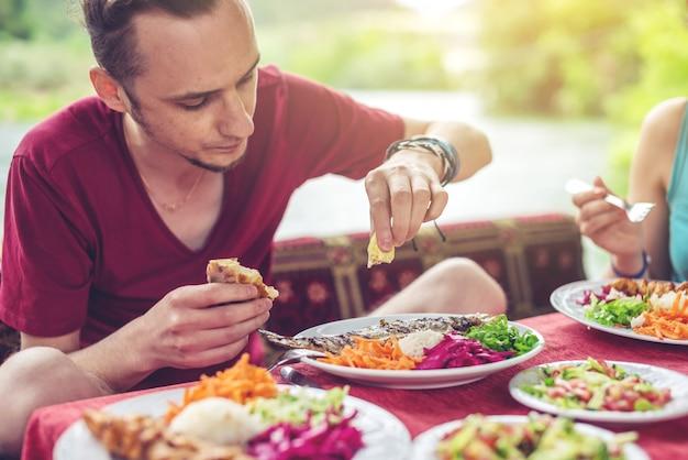 Junger mann isst gemüse und fisch im freien