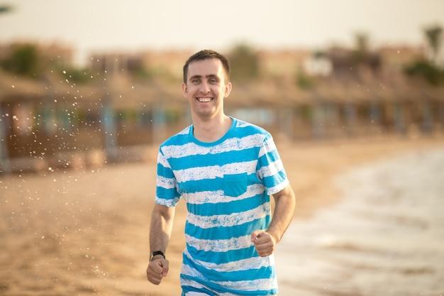Junger mann joggen durch die brandung