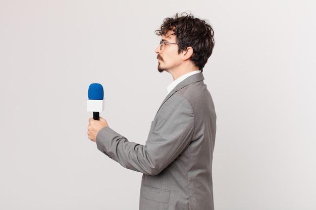 Junger mann-journalist auf profilansicht denken, sich vorstellen oder träumen