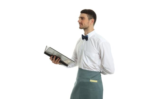 Junger mann kellner hält menü, isoliert auf weißem hintergrund.