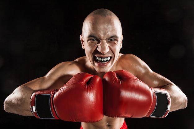 Junger mann kickboxen auf schwarz mit schutz im mund