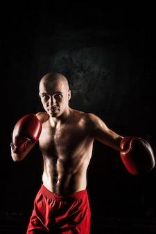 Junger mann kickboxen auf schwarz