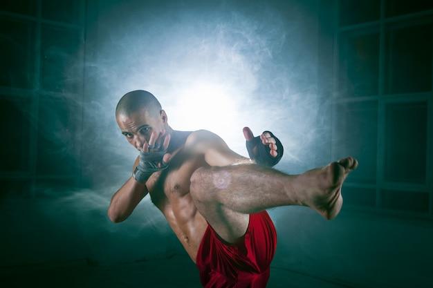 Junger mann kickboxen in blauem rauch