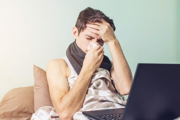 Junger mann krank mit einer erkältung im bett liegen