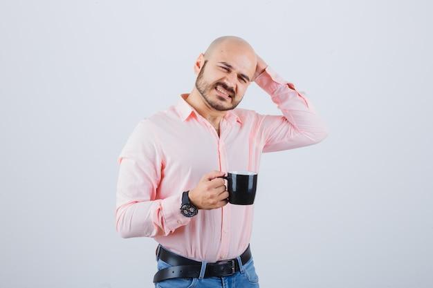 Junger mann kratzt sich am kopf, während er eine tasse in rosa hemd, jeans hält und nachdenklich aussieht, vorderansicht.