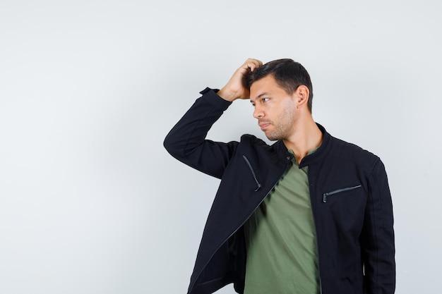 Junger mann kratzt sich am kopf, während er in t-shirt, jacke und gutaussehend, vorderansicht beiseite schaut.