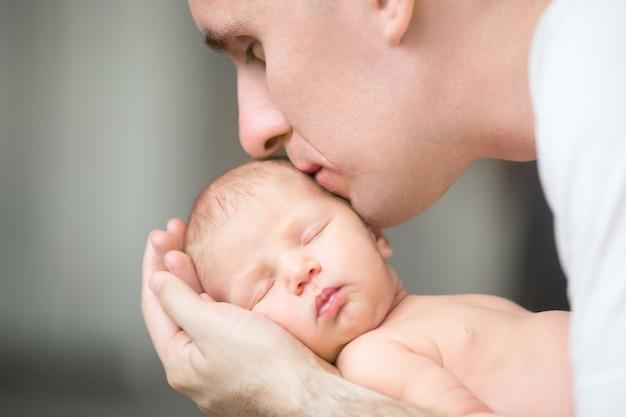Junger mann küsst ein neugeborenes, er hält in seinen handflächen