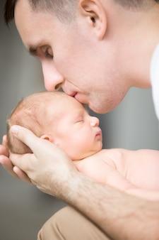 Junger mann küsst ein neugeborenes in seinen handflächen