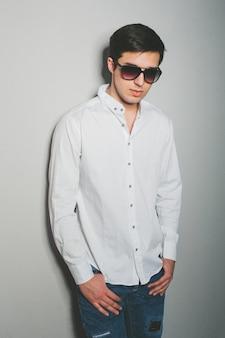 Junger mann kurz gesagt und weißes hemd lächelt, stehend nahe der wand mit gläsern