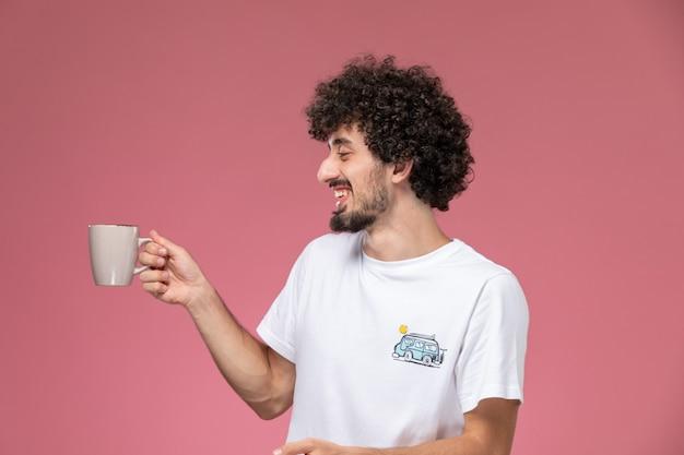 Junger mann lacht mit seiner tasse