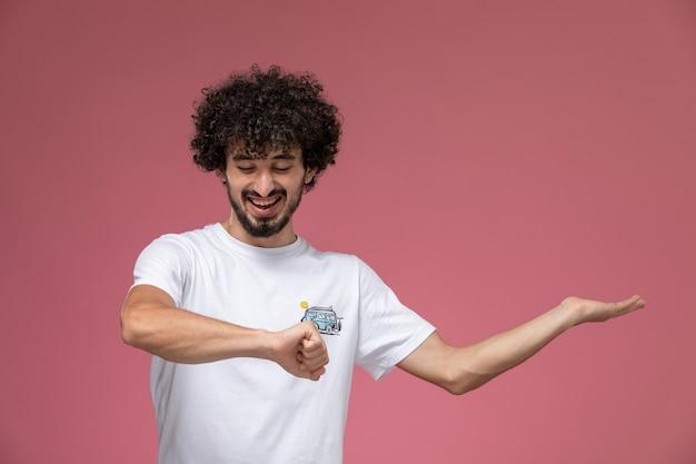 Junger mann lacht über sein handgelenk