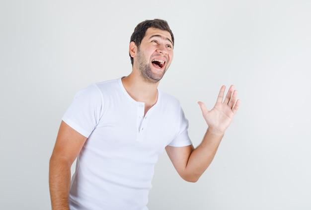 Junger mann lacht und hält hand offen im weißen t-shirt und sieht glücklich aus