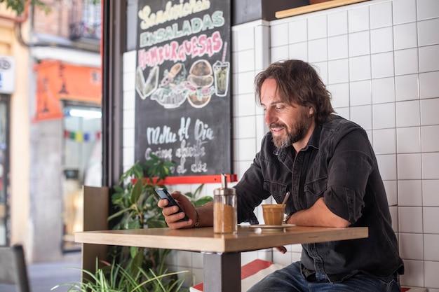 Junger mann lacht, während er das handy betrachtet und kaffee trinkt