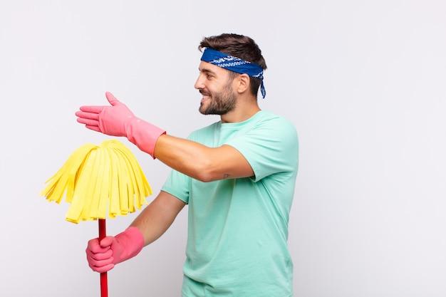 Junger mann lächelt, begrüßt sie und bietet einen handschlag an, um ein erfolgreiches geschäft, kooperationskonzept abzuschließen