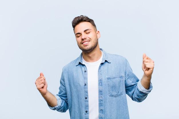 Junger mann lächelt, fühlt sich sorglos, entspannt und glücklich, tanzt und hört musik, hat spaß auf einer party über blauer wand