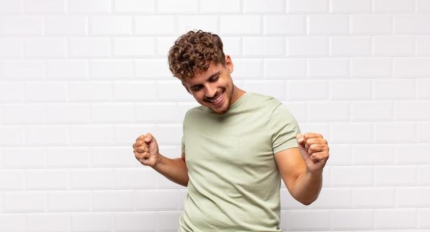 Junger mann lächelt, fühlt sich sorglos, entspannt und glücklich, tanzt und hört musik, hat spaß auf einer party