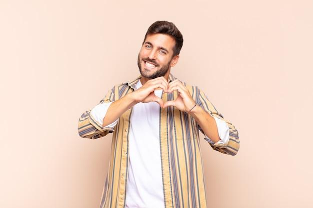 Junger mann lächelt und fühlt sich glücklich, süß, romantisch und verliebt, herzform mit beiden händen machend