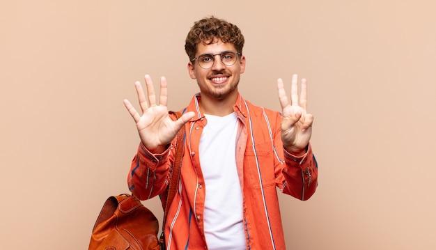 Junger mann lächelt und sieht freundlich aus, zeigt nummer acht oder acht mit der hand nach vorne und zählt herunter. studentenkonzept