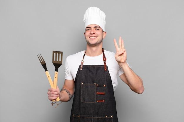 Junger mann lächelt und sieht freundlich aus, zeigt nummer drei oder drei mit der hand nach vorne und zählt herunter