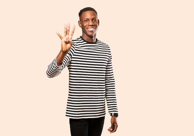 Junger mann lächelt und sieht freundlich aus, zeigt nummer drei oder dritte mit der hand nach vorne und zählt gegen beige wand herunter