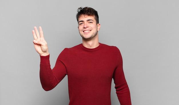 Junger mann lächelt und sieht freundlich aus, zeigt nummer drei oder dritte mit der hand nach vorne und zählt herunter