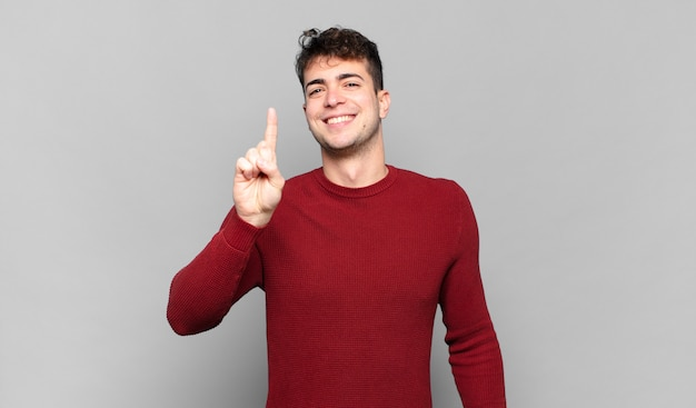 Junger mann lächelt und sieht freundlich aus, zeigt nummer eins oder zuerst mit der hand nach vorne, zählt herunter
