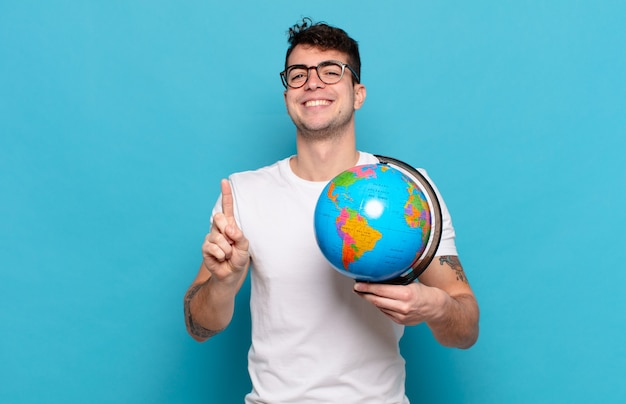Junger mann lächelt und sieht freundlich aus, zeigt nummer eins oder zuerst mit der hand showing