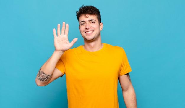 Junger mann lächelt und sieht freundlich aus, zeigt nummer fünf oder fünften mit der hand nach vorne, countdown