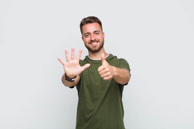 Junger mann lächelt und sieht freundlich aus, zeigt nummer sechs oder sechste mit der hand nach vorne, countdown