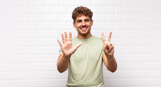 Junger mann lächelt und sieht freundlich aus, zeigt nummer sieben oder siebte mit der hand nach vorne und zählt herunter