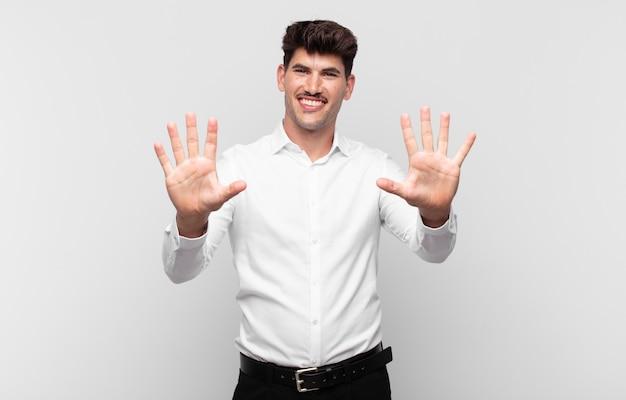 Junger mann lächelt und sieht freundlich aus, zeigt nummer zehn oder zehntel mit der hand nach vorne, countdown