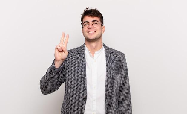 Junger mann lächelt und sieht freundlich aus, zeigt nummer zwei oder sekunde mit der hand nach vorne, countdown