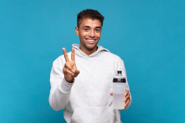 Junger mann lächelt und sieht glücklich, sorglos und positiv aus, gestikuliert sieg oder frieden mit einer hand. sportkonzept