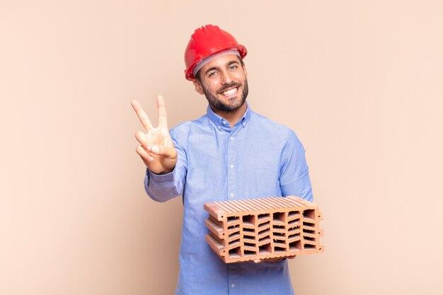 Junger mann lächelt und sieht glücklich, sorglos und positiv aus, gestikuliert sieg oder frieden mit einer hand.