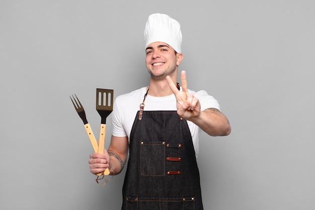 Junger mann lächelt und sieht glücklich, sorglos und positiv aus, gestikuliert sieg oder frieden mit einer hand