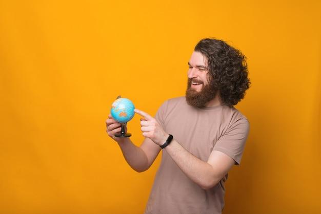 Junger mann lächelt und zeigt auf globus, nächster punkt zu reisen