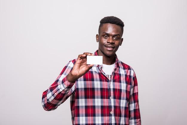 Junger mann lächelt und zeigt visitenkarte mit leerem kopienraum. isoliert