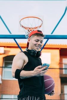 Junger mann lächelt, während er ein handy auf dem spielplatz nimmt