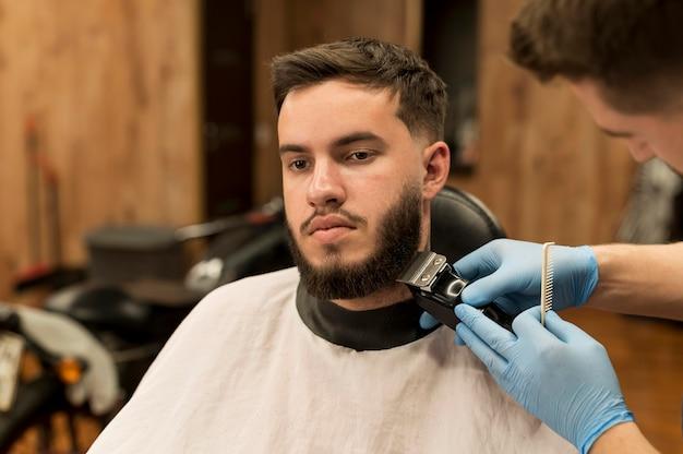 Junger mann lässt sich beim friseur seinen bart stylen