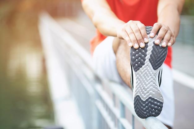 Junger mann läufer, der arm schulter und körper zum aufwärmen streckt, bevor er läuft oder auf straße im park trainiert. leichtathletik-übung. fitness und sport gesunder lebensstil konzept.