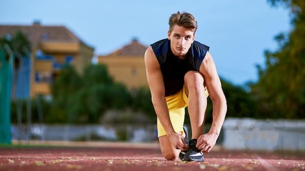 Junger mann läufer, der schnürsenkel am stadion bindet.