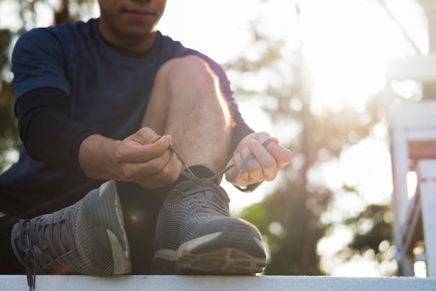 Junger mann läufer, der schnürsenkel bindet.