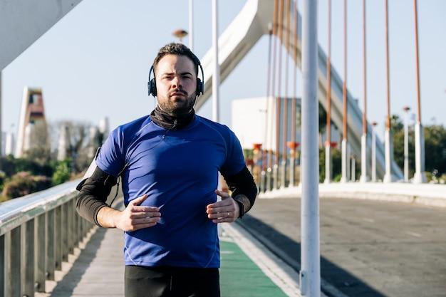 Junger mann läuft und hört musik in einem städtischen gebiet