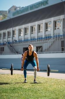Junger mann legt die messlatte im stadion höher, training im freien