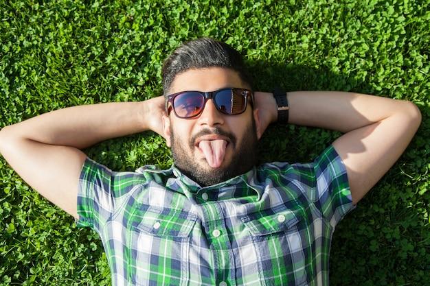 Junger mann legt sich auf den rasen und genießt die sommerzeit.