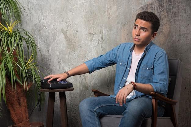 Junger mann legte den hörer auf und setzte sich auf einen stuhl. hochwertiges foto