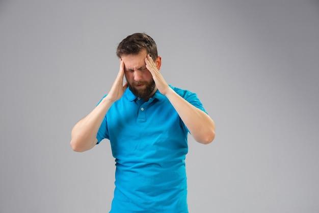 Junger mann leidet unter schmerzen fühlt sich krank und schwäche an der wand isoliert